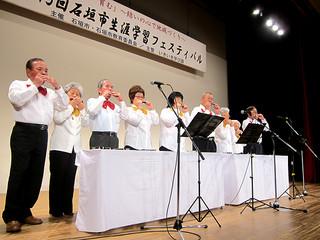 さわやかな音色と懐かしい曲で会場を楽しませた石垣市ハーモニカ愛好会のメンバー=8日午前、市民会館中ホール