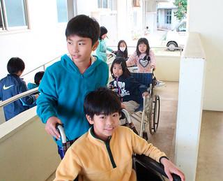 車いすを押してスロープを上る児童ら=10日午後、同校体育館
