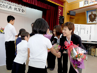 ちゅらネットの10周年記念式典で子どもたちから花束を贈られる平良智恵美さん、大城みゆきさん(右から)ら=15日午前、双葉公民館
