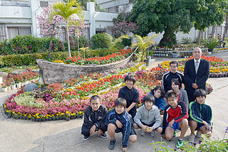 花メッセージコンテストで県知事賞に輝いた新川小学校の校門と栽培委員の皆さん=18日午後、同校