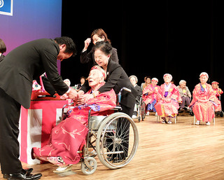 あやかりの杯の後、中山義隆市長に昆布を手渡す新城静枝さん=19日午後、市民会館大ホール