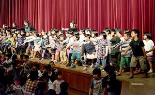 くにぶん木の会のメンバーと一緒に元気いっぱい「ドキドキドン!1年生」を踊る参加者たち=22日午後、市民会館大ホール