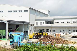 原料ヤードにサトウキビが積まれ、圧搾試験が行われている西表製糖工場=23日午後