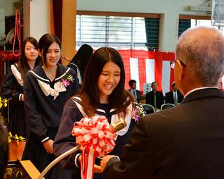 八重山農林高校の第77回卒業式で、渡久山修校長(右)から卒業証書を受け取る卒業生たち=1日午前、同校