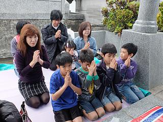 墓前にごちそうを供え、手を合わせる譜久山さん家族ら=6日午後、バンナ南側の飛び地区
