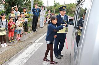 学校前を通過するドライバーにチラシを配り、不法投棄をしないように呼びかける富野小中学校の児童ら=9日午後