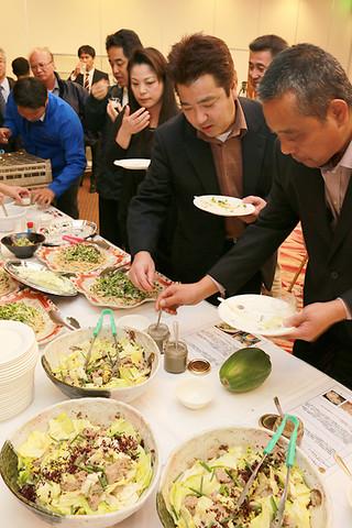 新特産品開発事業で試作した調味料と試作品を使った料理を味わう人たち=10日夜、南の美ら花ホテルミヤヒラ