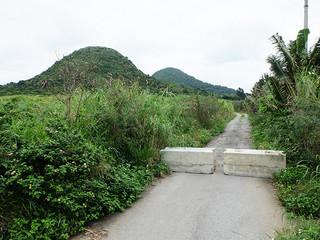 県道から伊原間牧場入り口に通じる道路。現在、通行できなくなっている=11日午後