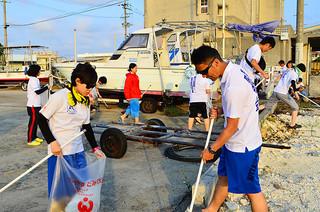 ボランティア清掃に汗を流す日本体育大学学友会アーチェリー部の部員ら=16日午後、登野城漁港