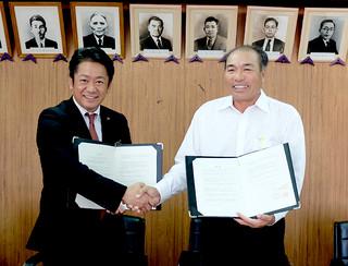 不発弾一時保管庫に関する合意書を締結し、握手する中山市長(左)と新里館長=16日夕、庁議室