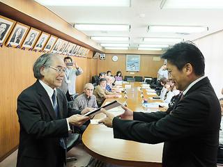 中山義隆市長に子ども・子育て支援事業計画案を答申する小倉隆一会長=16日午後、庁議室