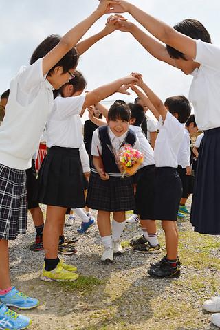 在校生の花道を笑顔でくぐり抜け、母校を後にする明石小学校の鈴木媛香さん=20日午前、同校