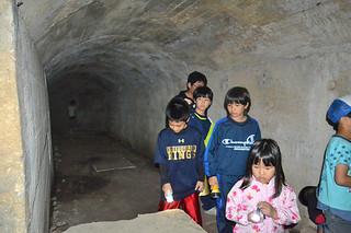平喜納飛行場の関連壕内を見学する子どもたち=22日午後、真栄里川良原地区