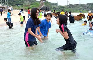 テープカットの後、一斉に海に飛び込み、初泳ぎに歓声を上げる子どもたち=22日午前、与那国町久部良ナーマ浜