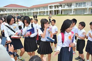 涙を流しながら花道を通り抜ける真喜良小学校の卒業生たち=23日午後、同校