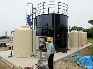 発酵槽(中央のタンク)と調整槽(左)、液肥用タンク(右)、制御盤(手前)などを備えるメタン発酵試験用プラント=23日午後、石垣市し尿処理場内