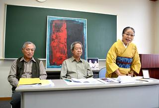 新城剛絵画展開催の経緯などを説明する妻の知子さん(右)ら=27日午後、大浜信泉記念館