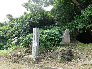 フルスト原遺跡の崖下にあるコンクリート柱と説明版。右側のトンネル壕を遺跡と勘違いする観光客もいるという=18日午前