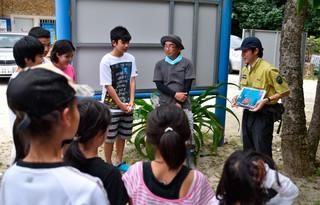 富野小中学校の児童生徒に米原海岸での乱獲について現状を説明する若松上席自然保護官(右)=5日午後、米原海岸