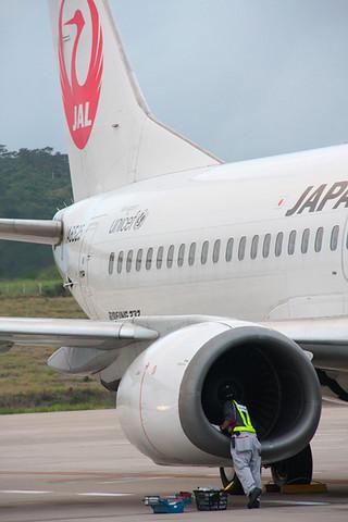 離陸を中断して駐機場に引き返したJTA機。右エンジンの点検をする整備士=7日午後6時23分、南ぬ島石垣空港