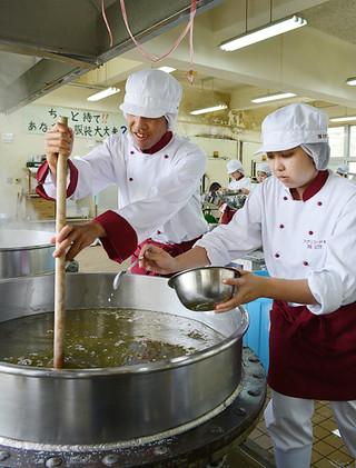 サトウキビの搾り汁を煮詰める八重山農林高校アグリフード科の3年生=17日午後、同校