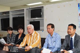 「辺野古基金」の寄付金額について発表する新里米吉氏(中央)ら県議会与党メンバー=17日午後、県庁