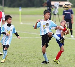 第1回FC琉球カップ2015カテゴリーAの白保轟FCA—川平小学校A(白)。後半終了間際ライン際で足を出してボールキープを狙う=5日午前、サッカーパークあかんま