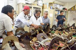 馬具を研究する会で、持ち寄った馬のくらの特徴などを確認した八重山愛馬クラブの会員ら=4日午後、平得公民館