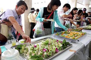 八重山調理師会のゴーヤを使った料理を試食する人々=8日午前、ゆらてぃく市場