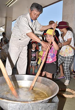 黒糖の日を前に行われたイベントで黒糖作りに挑戦した子どもら=9日午前、JAファーマーズマーケットゆらてぃく市場