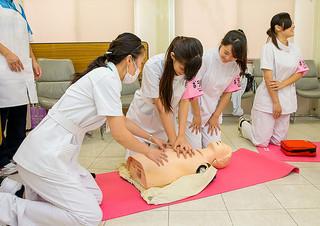 かりゆし病院の「ふれあい看護体験」で、人形を使って心肺蘇生を体験する高校生ら=13日午後、同病院