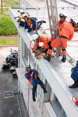 3段ばしごなどを駆使して要救助者をつり上げる消防隊員=13日午後、市消防本部