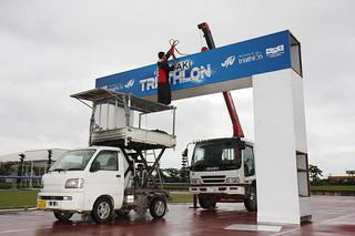 24日に迫ったフィニッシュゲートが設置されるなど石垣島トライアスロン2015の会場設営が急ピッチで進む市中央運動公園陸上競技場=22日午後