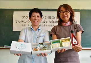 ブライダル商品として販売が決まり、独自商品を手にするPatio石垣島の小村智子代表とグリーンズファームの柳田千晶代表(左から)=農村青少年教育センター