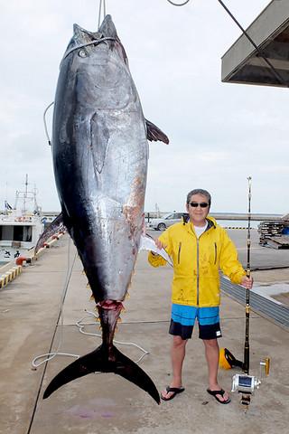 7時間余の格闘の末、釣り上げた本マグロと松方弘樹さん=27日午前10時50分ごろ、八重山漁協前