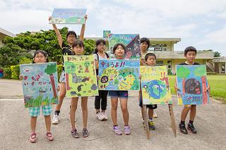 できあがった不法投棄防止看板を掲げる児童ら=28日午後、富野小中学校
