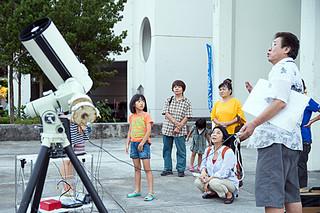 天体観望会で八重山星の会の通事安夫さん(右)から話を聞く参加者=29日夕、石垣市役所ピロティ