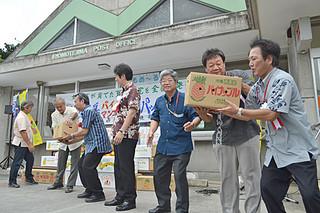 ゆうパックの引き渡しなどを行う出席者ら=6日午後、西表島郵便局前