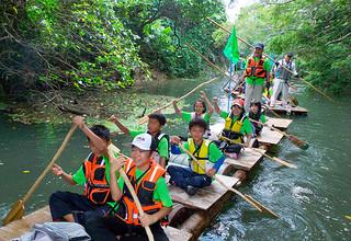 手作りのいかだとカイで宮良川の川下りを楽しんだ宮良小6年の児童ら=7日午前、宮良川(同校PTA提供)