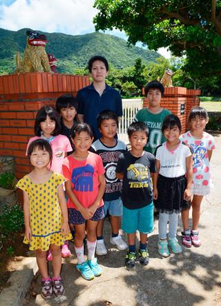 平久保小のシーサーを修復した新里龍生さん(中央)と喜ぶ同校の児童たち=8日午後、同校