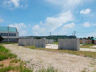 基礎工事を終えた与那国島歴史文化交流資料館の建設地。左端は与那国中体育館=16日午後、祖納