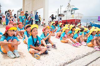 東一組が練習する転覆ハーリーを応援するあまかわ幼稚園の園児ら=17日午前、登野城漁港