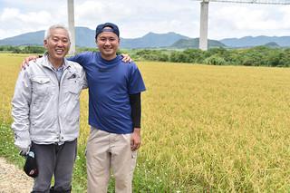 認証を受けた特栽米のほ場で笑顔をみせる生産者の通事浩大さん(右)と技術指導した山田義哲さん=5月28日午前、白保にある通事さんのほ場