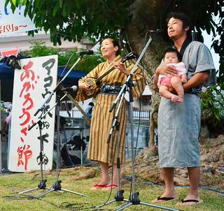 長女の羽花ちゃんと一緒に舞台に上がり、「あがろうざ節」を歌い上げる宮城拓矢・奈美子さん夫婦=20日夕、登野城