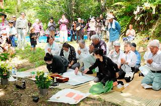 字石垣の避難先を訪ね、犠牲者を供養する参加者たち=21日午前、外山田山中のカーラフターゼー