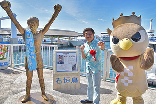 国際ボクシング殿堂入りを記念したパネルの横に立ち、ファイティングのポーズを取る具志堅用高氏=22日午前、石垣港離島ターミナル