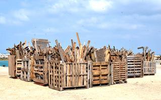 貨物輸送のために使われた後、港湾内に積まれた「パレット」。木くずの処理が課題となっている。=資料写真・2015年2月、黒島港