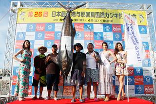130㌔のクロカワカジキを釣り上げ、親指を立てポーズをとる梶原雅仁さん(右から3番目)=4日午後、久部良漁港特設会場