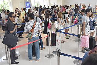 空の便が運航再開し、観光客や地元利用客で混雑する航空各社のカウンター=11日午後、南ぬ島石垣空港