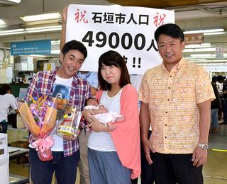 人口4万9000人突破の記念セレモニーで祝福された宇根底沙和ちゃんを抱く弘美さん(中央)と忍さん(左)=13日午前、市役所1階ロビー
